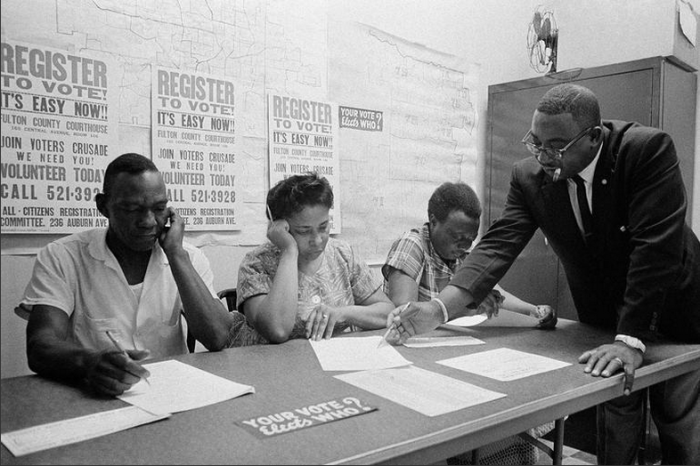 Rev. Fred C. Bennette Jr. (R) instructs Atlanta African Americans how to fill out registration forms which will enable them to vote on Jul. 22, 1963. Similar classes were held in other cities in an effort to increase African American voting power, which is a powerful weapon in his fight against segregation. Seated from left are Austin L. Hayes, Mrs. Dollie M. Shepherd, and Mrs. Hattie Ward. Photo by Horace Cort/AP
